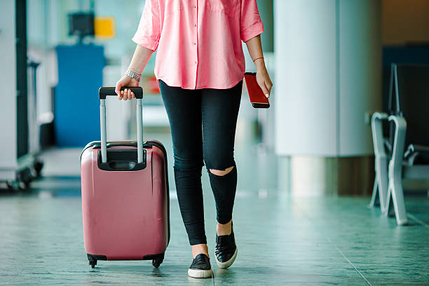 Passenger with passports and boarding pass and pink baggage stock photo
