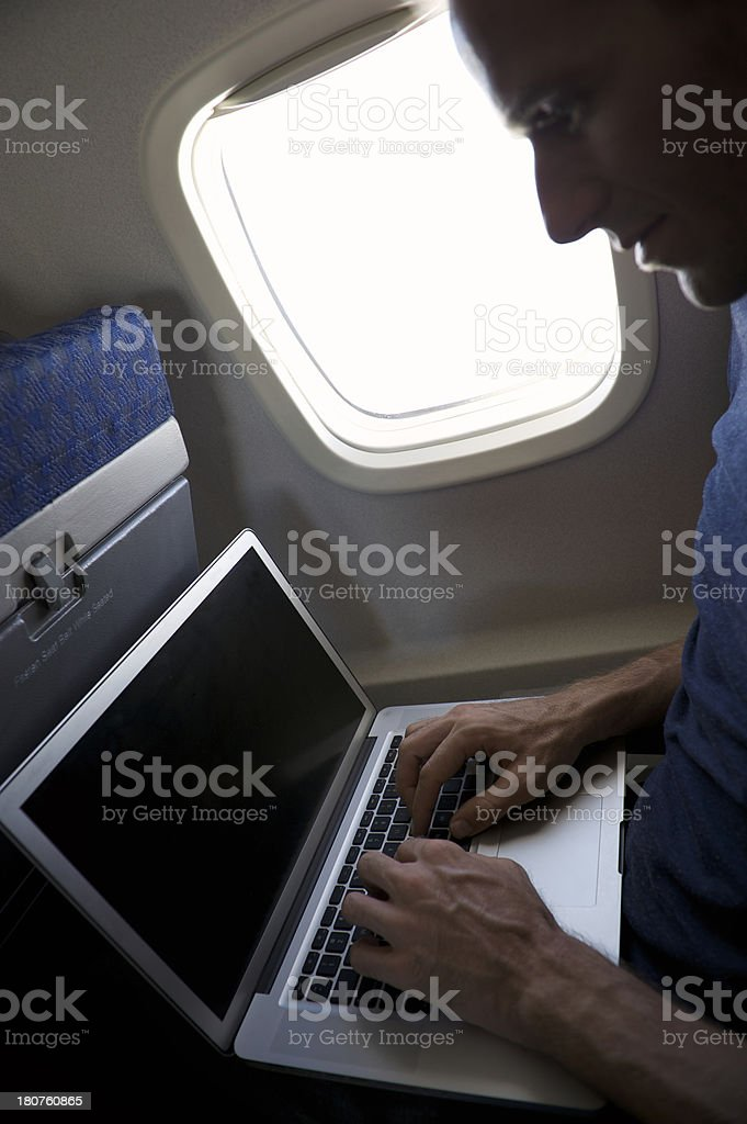 Passenger Works Typing on Laptop in Airplane Window Seat royalty-free stock photo