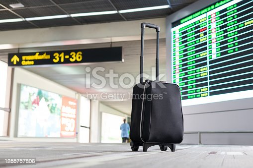 Passenger luggage wait and look at terminal gate information board checking for her flight in international airport. Suitcases in the departure lounge, holiday vacation concept, traveler suitcases
