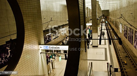 istock Passengers and tourists in Bockenheimer Warte - Senckenberg Museum train station waiting for a delayed train heading to Frankfurt am Main Hauptbahnhof (Frankfurt central station) - Germany. Direction to Enkheim to the left 1164173587