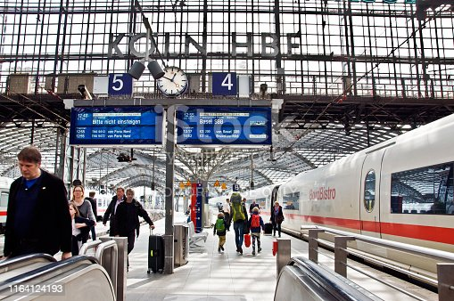 istock Passengers and tourists train platforms 4 and 5 near an escalator train at Koeln Hauptbahnhof (Cologne Central Station) - Germany. Deutche Bahn ICE high speed train heading to Basel SBB Switzerland on platform 1164124193