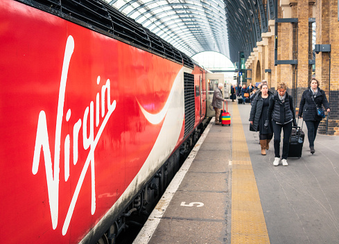 London, UK - Passengers walking along the platform at King's Cross station, having disembarked from a recently arrived Virgin East Coast Train.