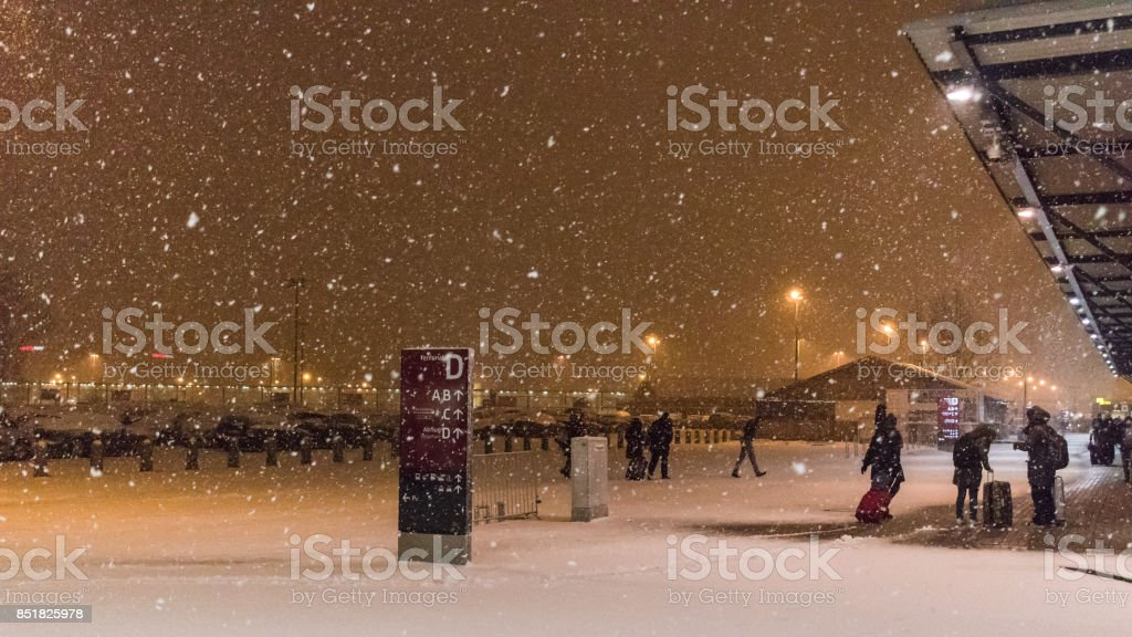 Passengers at Schönefeld Airport crossing from one terminal to next during heavy snow storm stock photo