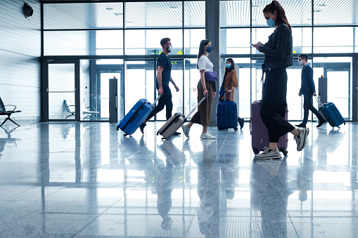 People traveling by plane during COVID 19, wearing N95 face masks, carrying luggage in airport terminal.