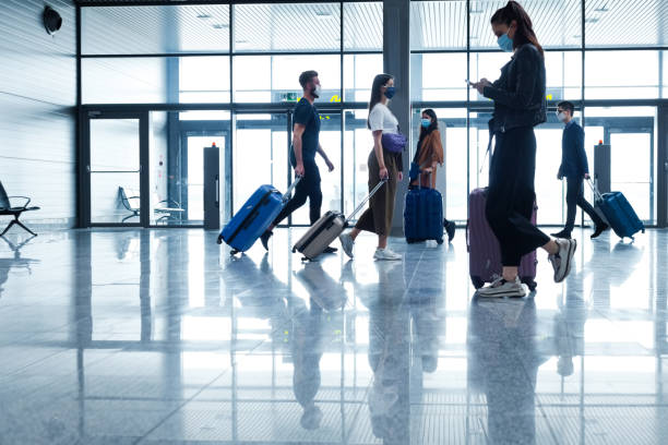 Passengers at the airport with luggage, wearing N95 face masks stock photo