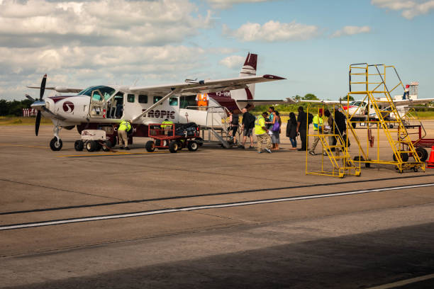 Passengers board small Tropic Air Airplane departing from Philip S W Goldson Airport in Belize, Central America.