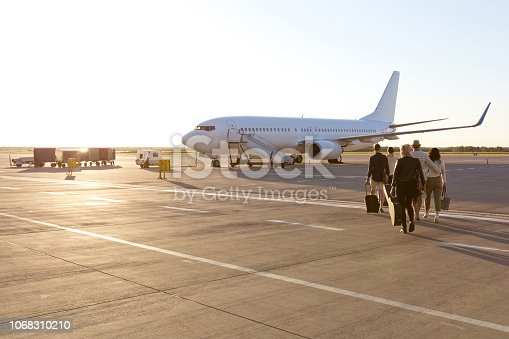 Outdoor shot of passengers boarding a flight at sunset. Airplane in the background