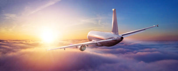 Passengers commercial airplane flying above clouds stock photo