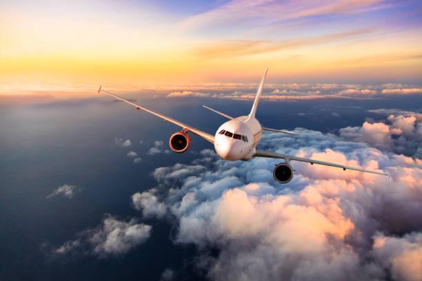 avión comercial de pasajeros volando por encima de las nubes - avión fotografías e imágenes de stock