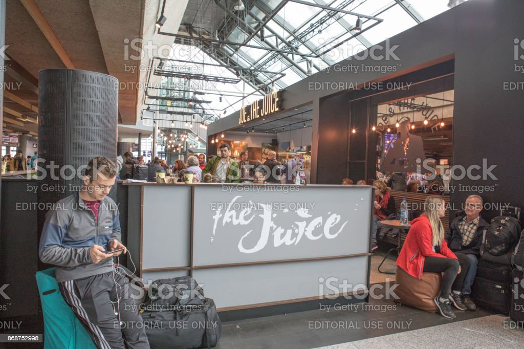 Passageiros comendo e usando a tecnologia enquanto aguarda a partida de voos no Aeroporto Internacional de Keflavík, Islândia - foto de acervo