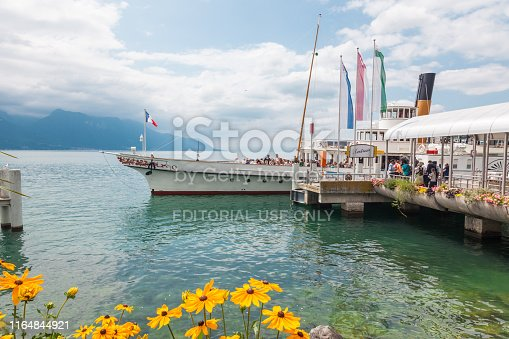Passengers embarking the elegant Belle Epoque restored retro paddle boat named Italie moored in Montreux, Lake Geneva (lac Leman), Vaud, Switzerland with beautiful summer flowers on waterfront