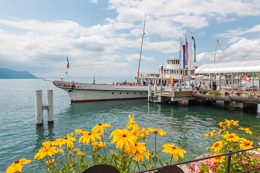 Passengers embarking the retro paddle boat named Italie moored in Montreux, Lake Geneva (lac Leman), Vaud, Switzerland with beautiful summer flowers on waterfront