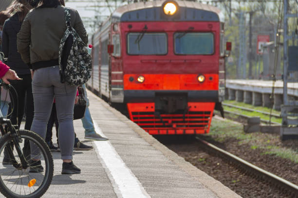 passengers expect the arriving train on the platform of the station passengers expect the arriving train on the platform of the station in clear summer day electric train stock pictures, royalty-free photos & images