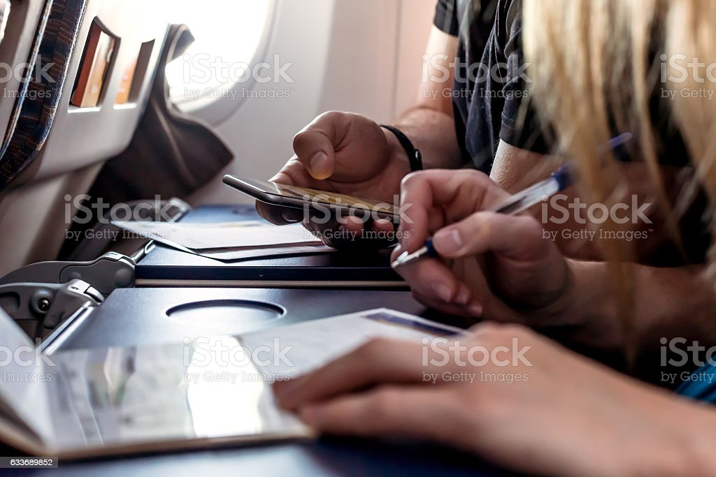 Passengers filling in Immigration Forms in the Aircraft stock photo