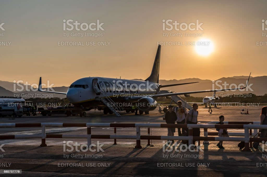 Passengers get off Boeing 737-800 plane on runway at sunset foto stock royalty-free