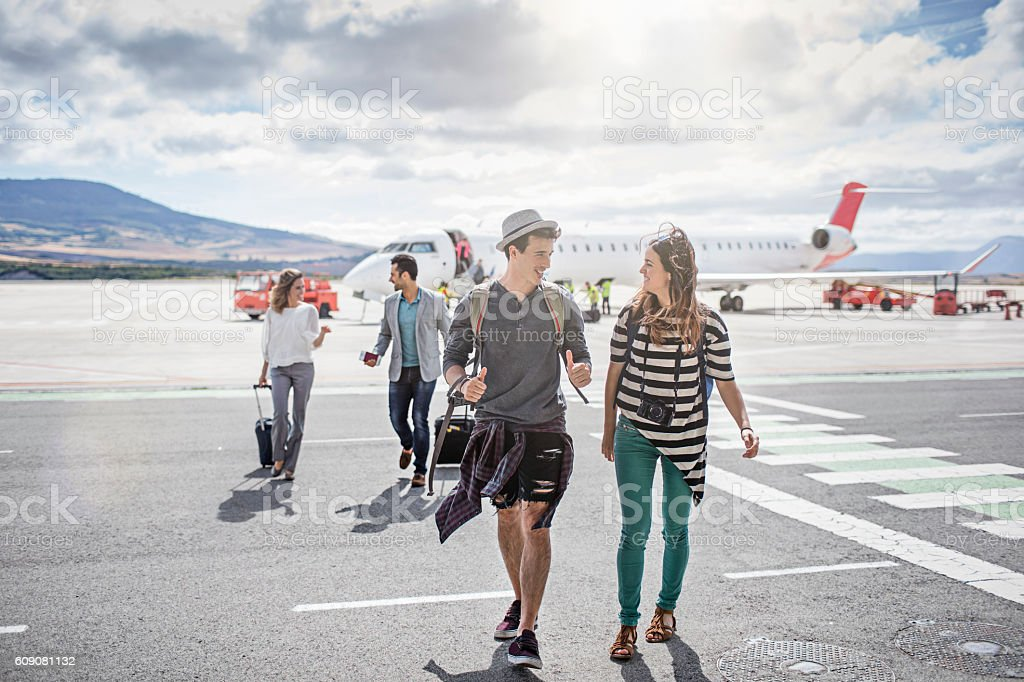 Passengers getting out of the airplane on a sunny day stock photo