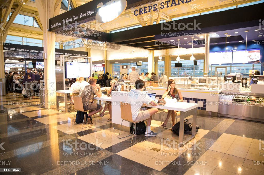 Passengers in airport food court using their computer electronics
