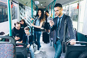 Young people traveling with public transport, using smart phones.