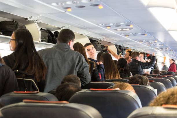 Passageiros em uma linha deixando um avião. - foto de acervo