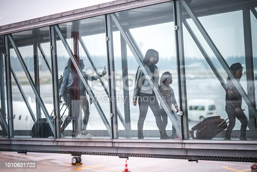 Passengers walking on footbridge at airport terminal. People with luggage are moving towards other part of building. They are seen through glass window.