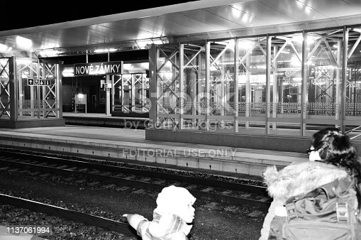 istock Passengers (incl a mother and children) patiently waiting for a night train at Nove Zamky train station (near Bratislava) - Slovakia. Black and white image 1137061994