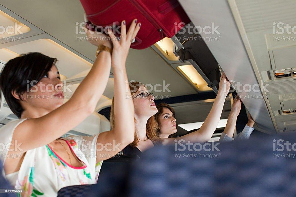 Passengers putting luggage in lockers on plane stock photo