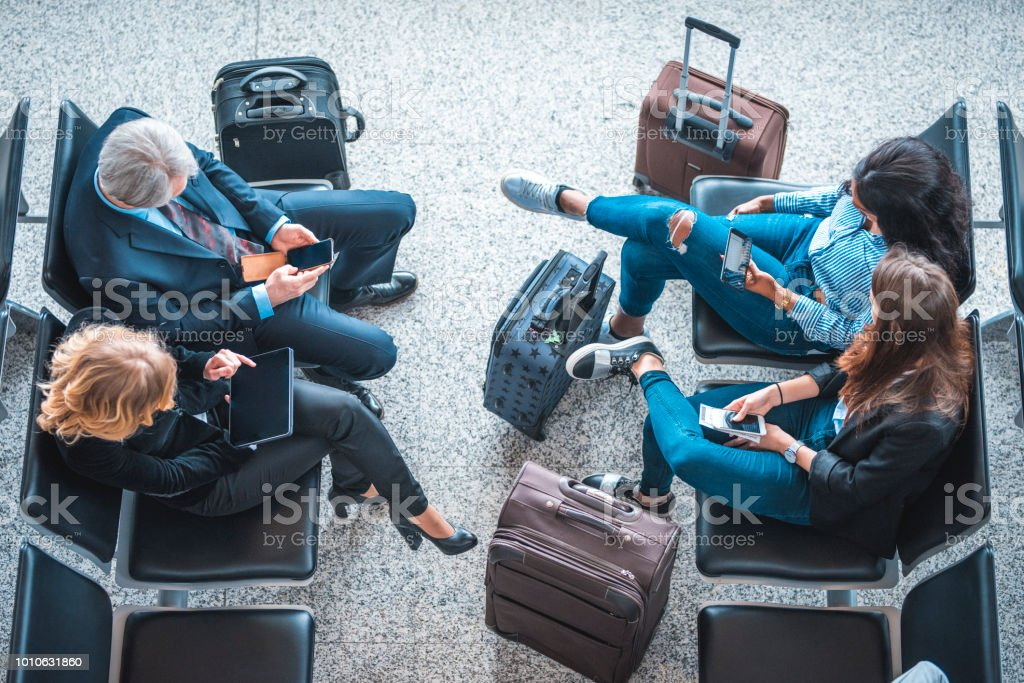 Passengers sitting on seats at airport terminal stock photo