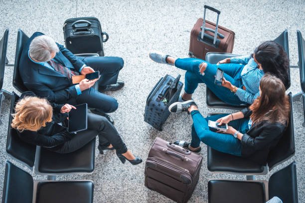 passengers sitting on seats at airport terminal - business travel stock photos and pictures