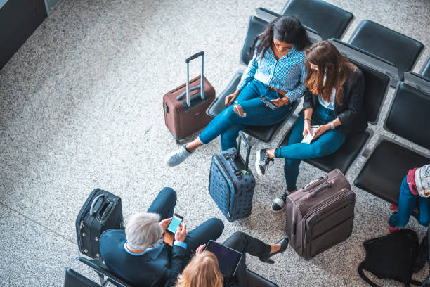 Passengers sitting on seats in departure area High angle view of passengers waiting for flights at departure area. People are sitting on seats at airport terminal. They are using technologies. airport stock pictures, royalty-free photos & images
