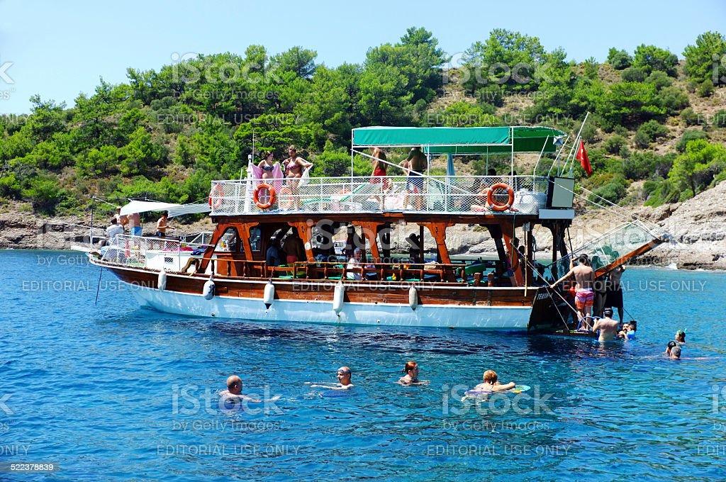 Passengers swimming around their boat stock photo
