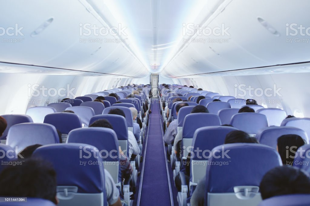 view of the inside of modern commercial airliner with passengers...