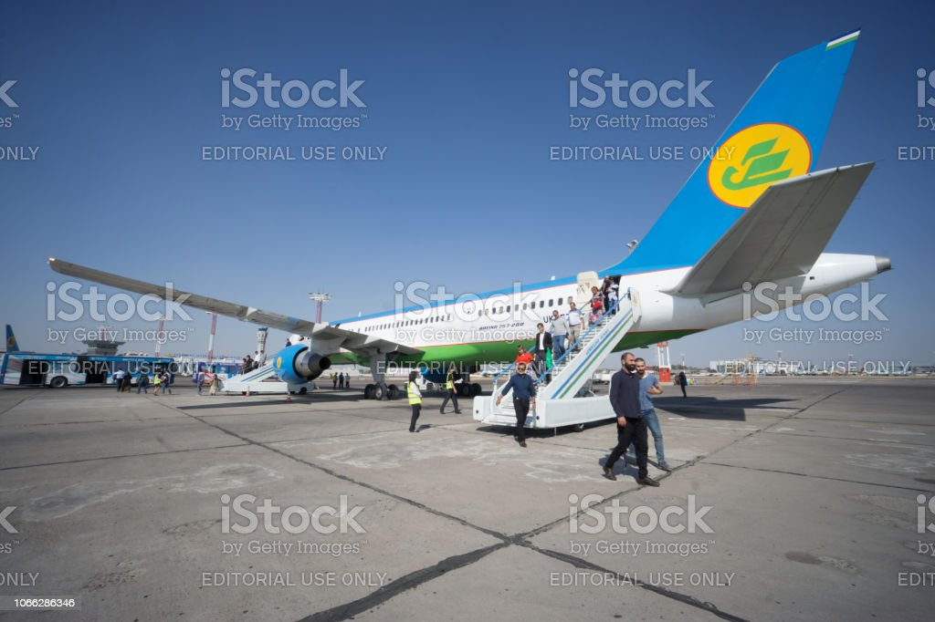 Passengers unboard the plane in Tashkent Airport stock photo