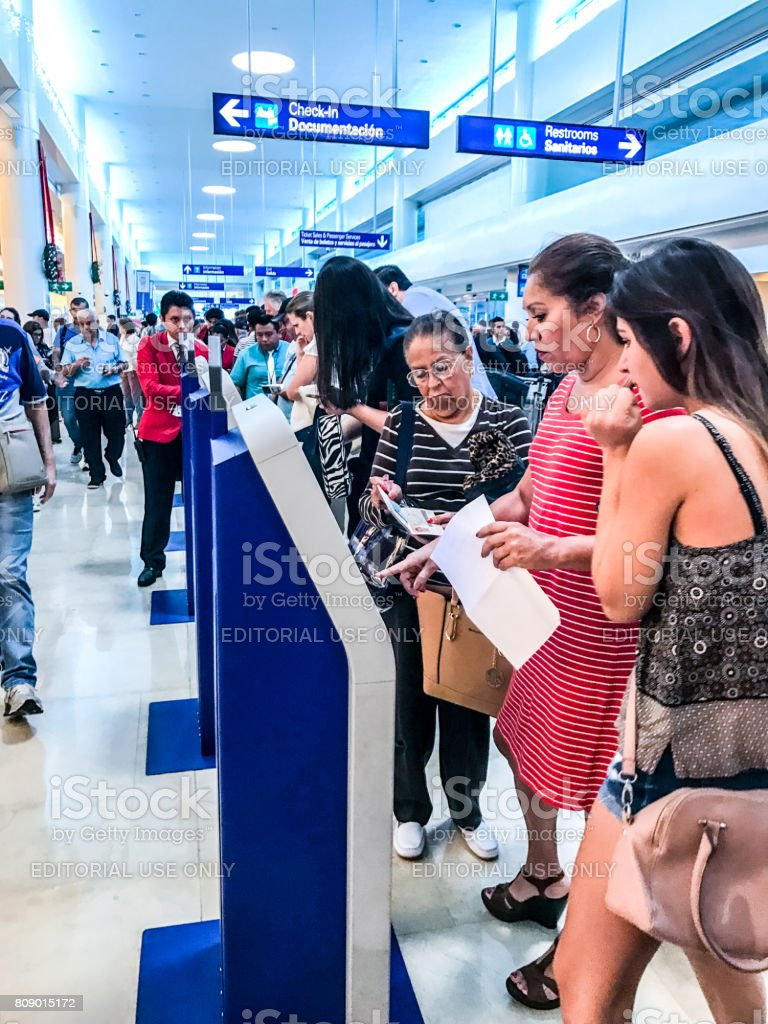 Passengers using self check-in machines in Cancun International Airport, Mexico stock photo