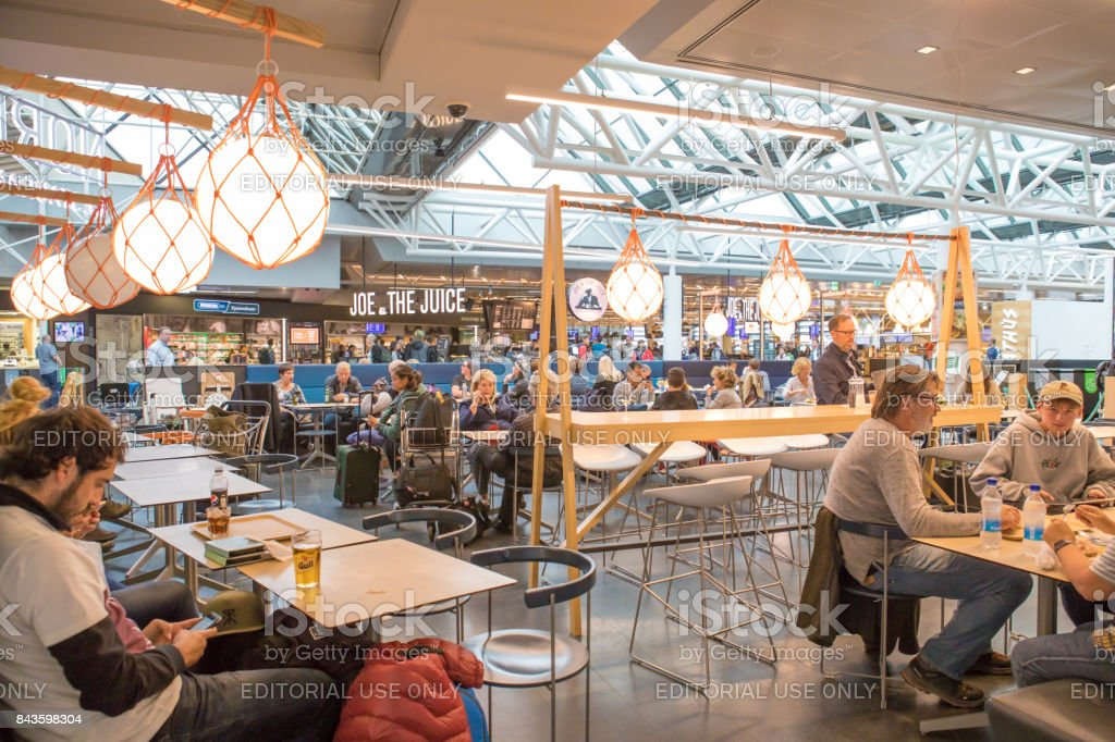 Passengers using technology, eating and drinking while waiting for departing flights at Keflavik International Airport, Iceland stock photo