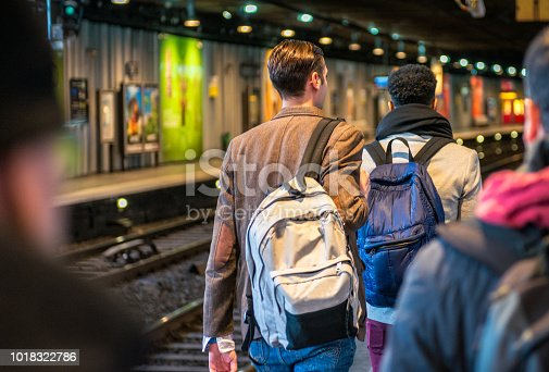 A rear view of passengers on the platform of a subway station in Paris, France.