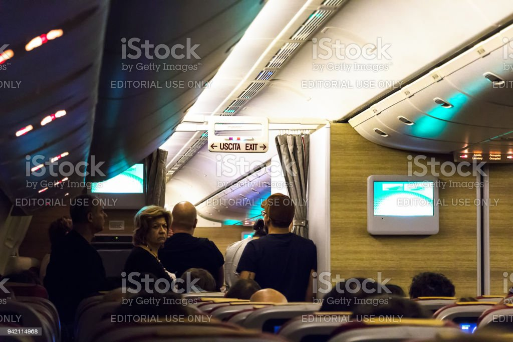 Passengers waiting for a toilette on a long flight. - foto stock