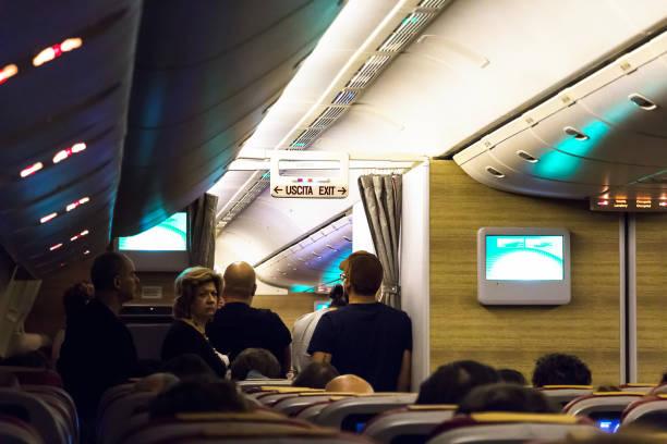 Passageiros esperando uma toilette em um voo longo. - foto de acervo