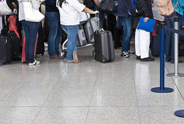 Passengers waiting in line to check in with luggage stock photo