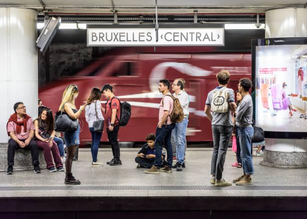 Les passagers qui attendent sur une plate-forme à la gare centrale de Bruxelles comme un train à grande vitesse Thalys passe. - Photo