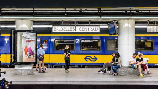 Les passagers qui attendent sur une plate-forme à la gare centrale de Bruxelles tandis qu'un train hollandais est stationnement. - Photo