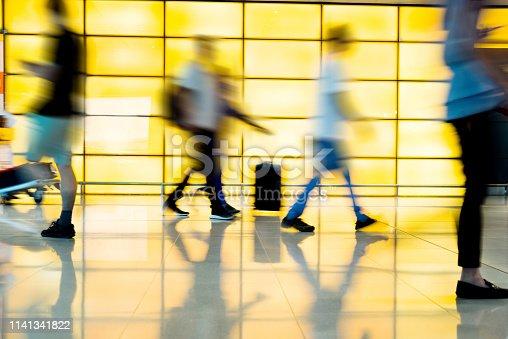 Passengers walking in modern corridor.
