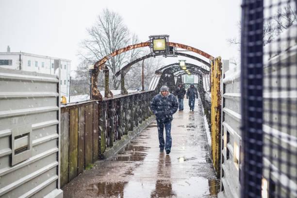 passagers à pied dans la neige de l'hiver de l'est sortie de la gare de welwyn garden city, uk - pont gênes photos et images de collection