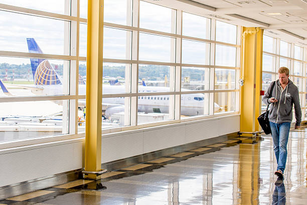 Passengers walking through a bright airport Washington, DC, United States - October 4, 2014: DCA, Reagan National Airport, Washington, DC - View out airport window to airplanes and ramp operations ronald reagan washington national airport stock pictures, royalty-free photos & images