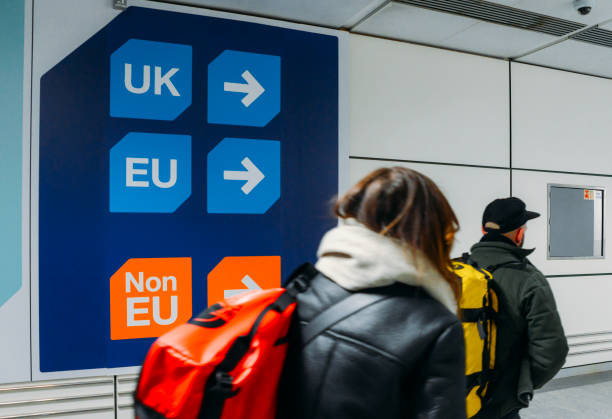 Passengers walks past sign prior to immigration control pass a si stock photo