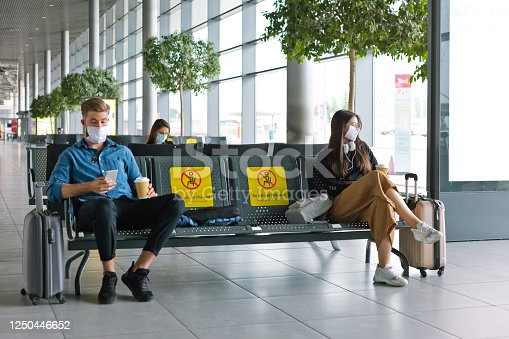 People traveling by plane during COVID 19, wearing N95 face mask, using a smart phone in airport waiting area.