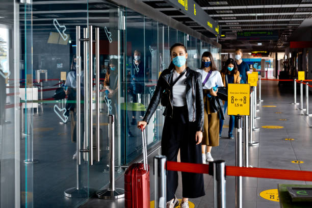 Passengers wearing N95 face masks waiting in line at airport terminal stock photo