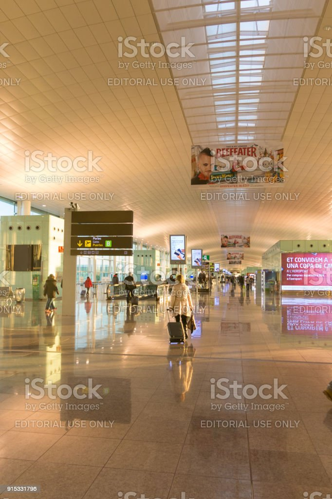 Passengers with luggage in Barcelona International Airport El Prat interior . Airport is one of the biggest in Europe stock photo