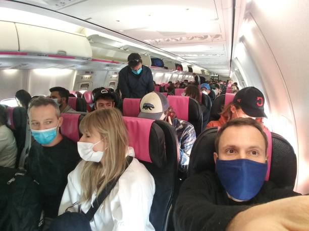 Passengers with masks inside an airplane stock photo