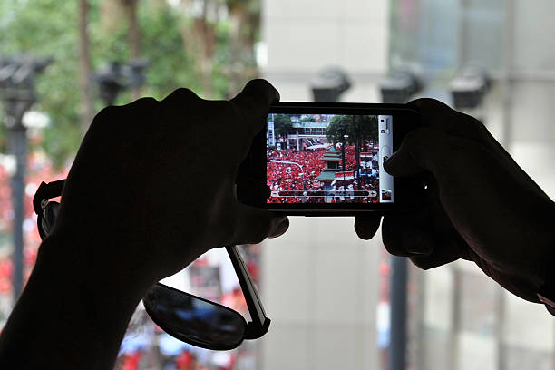 Passerby Uses Smartphone to Photo Political Rally stock photo