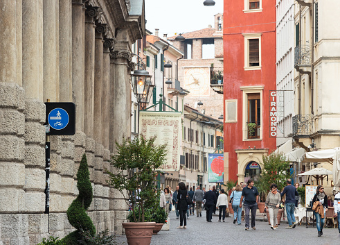 Passersby And Tourists Walk Along Rome Street Leading From The Arena To The Watchtower Of Castelvecchio Fortress In Verona Italy Stock Photo - Download Image Now